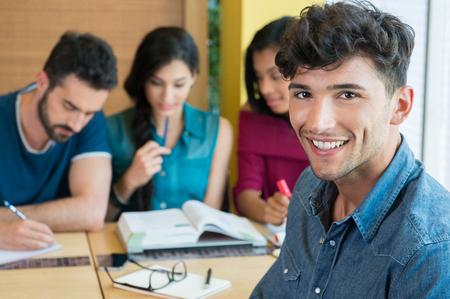 若い男がカメラ目線のクローズ アップ ショット。カジュアルな笑顔で幸せな男子学生。バック グラウンドで他の学生と笑みを浮かべてハンサムな