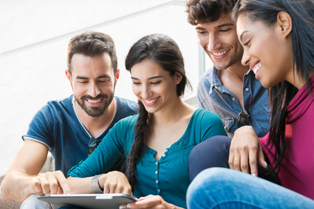 Closeup shot of young men and women looking at digitaltablet. Happy smilin friends sitting outdoor using digital tablet.   Happy young woman pointing on a digital tablet. Stock Photo