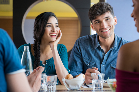 restaurant dining: Closeup shot of young women and men having meal. Happy smiling friends eating together at restaurant. Girls and guys are having fun during lunch. Stock Photo