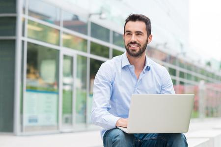 ノート パソコンで外に座っている若い男の肖像画。彼が離れています。ノート パソコンに座っている若い男に焦点を当てるとフィールドの浅い深さ