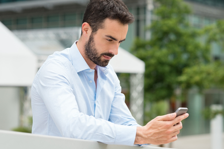 Closeup shot of young man messaging on smartphone. Happy smiling businessamn looking at smart phone leaning against a railing outdoor. Handsome young man using cellphone in a urban scene. Stock Photo