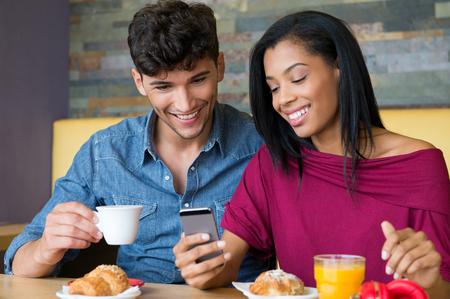 colazione: Primo piano ha sparato di giovane coppia felice guardando il telefono cellulare seduta sul tavolo della colazione presso bar. Sorridente matura la colazione al bar con brioche e una tazza di caffè. Ritratto di giovane coppia sorridente e guardando smart phone durante la colazione.