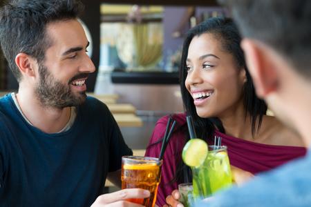 persona alegre: Retrato de hombre joven feliz y mujer sosteniendo copas de c�ctel. Amigos que beben un bebidas alcoh�licas en el bar. Sonriente joven hombre y mujer beber jugo y sonriente. La hora del aperitivo.