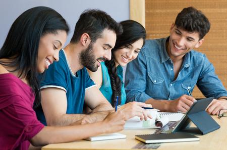 biblioteca: El primer tiró de hombre joven y una mujer que discute en la nota. Estudiantes sonrientes felices que preparan el examen. Equipo de estudiantes que estudian juntos para el examen de la universidad.