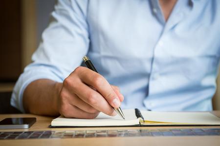hombre escribiendo: El primer tiró de un hombre que toma abajo nota en un organizador personal. Escritura de la mano del hombre joven en el diario. Poca profundidad de campo con enfoque en el hombre la mano derribar nota. Cerca de la mano de un hombre de negocios por escrito en un plan de negocios.