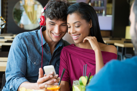 listening music: Closeup shot of young couple listening to music with mobile phone at coffee bar. Young man and african woman looking at smartphone at café. Happy young couple listening music with headphones. Stock Photo