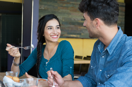 Closeup shot of young woman and man in casual having meal. Loving couple looking at eachother during the lunch. Happy smiling couple having lunch at restaurant. Stockfoto
