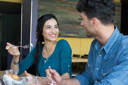 comiendo: Primer tirado de la mujer joven y el hombre en ropa de tener comida. Amante de la pareja mirando entre si durante el almuerzo. Feliz pareja sonriente almorzando en el restaurante.