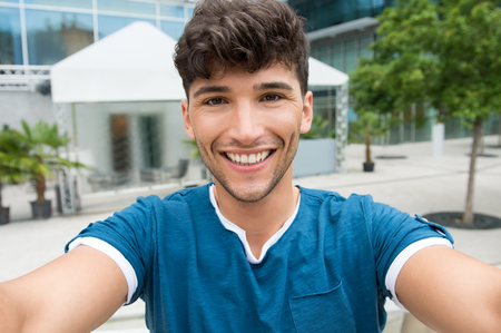 Detailní záběr pohledný mladý muž se selfie v centru města. Guy je fotografování vlastní venkovní. Malá hloubka ostrosti se zaměřením na usmívající se mladý muž s selfie.