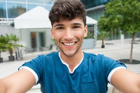 Gros plan de beau jeune homme de prendre une selfie dans le centre-ville. Guy est en photo en plein air. Faible profondeur de champ avec un accent sur souriant jeune homme de prendre selfie.