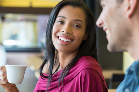 two men: Closeup shot of young woman drinking a cup of coffee at café. Young couple having breakfast at coffee bar. African young woman smiling at her boyfriend while drinking an espresso. Stock Photo