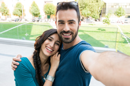 Closeup shot of young couple take selfie outdoor. Young man taking a photo with his girlfriend. Happpy smiling couple taking a selfie in a summer day. Standard-Bild