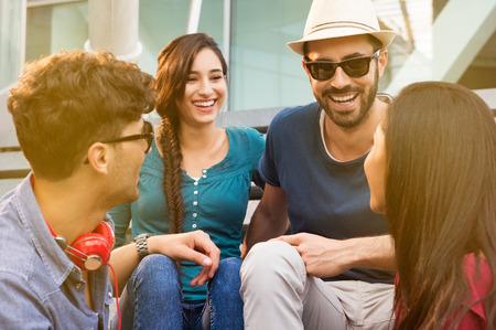 personas reunidas: Retratos de jóvenes amigos felices sonriendo y sentados en la escalera que se divierten. Mujeres y hombres que ríen junto al aire libre en un día de verano. Sonriendo las muchachas y los muchachos que se divierten. Sentado en la escalera
