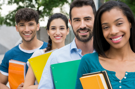edukacja: Closeup strzał studentów stojących w jednym rzędzie z książek. Szczęśliwa i uśmiechnięta grupa mężczyzn i kobiet posiadających książki outddor. Happy młodych przyjaciół posiadania książki i notebooka poza uniwersytetem.