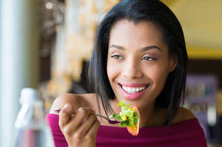 Closeup shot of young woman eating fresh salad at restaurant. Healthy african girl eating salad and looking away. Smiling young woman holding a forkful of salad. Health and diet concept. Woman ina a lunch break. Banque d'images