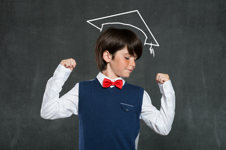 achieves: Closeup of boy flexing his muscles isolated on blackboard. School boy achieves his educational goals. Cute successful school boy showing off his arms strength over blackboard. Stock Photo