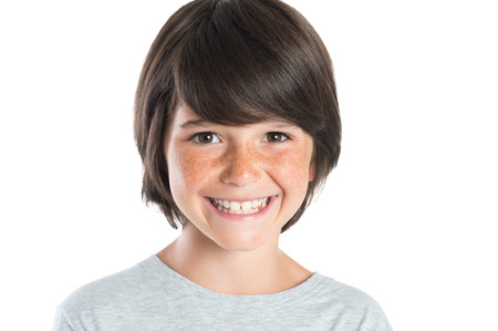 Detailní záběr z malého chlapce s úsměvem s pihami. Portrét šťastné chlapce při pohledu na kameru na bílém pozadí. Šťastný roztomilý chlapec s hnědými vlasy stojící proti bílému pozadí.