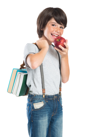 Closeup of smiling little boy eating red apple. Portrait of happy schoolboy holding the books and looking at camera. Happy cute boy with freckles holding apple and book isolated on white background. Scholar back to school. Stock Photo