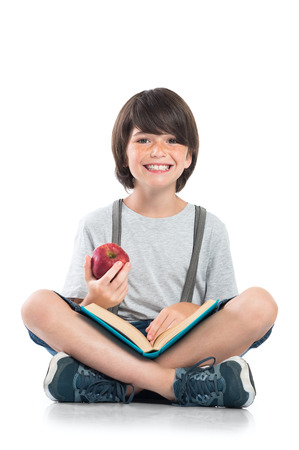 Closeup of smiling little boy studying isolated on white background. Portrait of laughing schoolboy sitting on floor and doing homework. Happy young boy eating a red apple and looking at camera with funny face. Foto de archivo