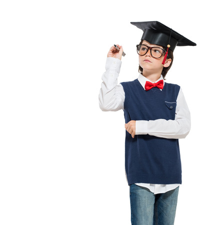 graduated: Graduated little boy wearing mortarboard and holding pen isolated on white background. Serious scholar boy writing with pen your message over white background. Concentrated schoolboy wearing graduation hat and writing on copy space. Stock Photo