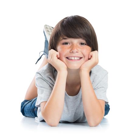 Close-up van lachende jongetje met sproeten liggend op een witte achtergrond. Gelukkig leuk mannelijk kind liggend op witte vloer en kijken naar de camera. Portret van een slimme jongen. Schattig blanke jongen liggend met de handen op de kin.