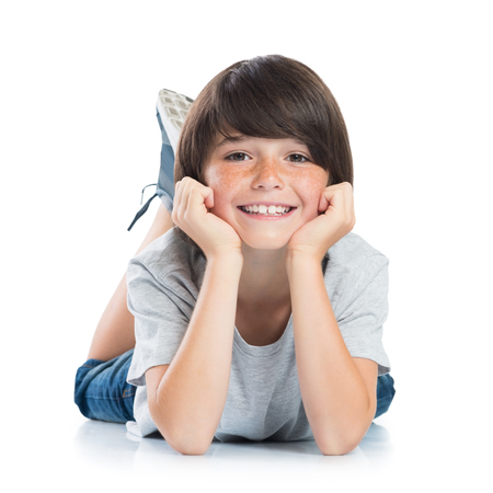 Closeup of smiling little boy with freckles lying on white background. Happy cute male child lying on white floor and looking at camera. Portrait of a smart young boy. Adorable caucasian kid lying with hands on chin.