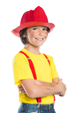 fireman: Closeup of smiling boy wearing firefighter helmet isolated on white background. Happy little fireman looking at camera with armcrossed.