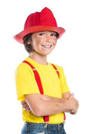 bombero: Primer plano de la sonrisa ni�o llevaba casco de bombero aislado en el fondo blanco. peque�o bombero feliz mirando a la c�mara con armcrossed.