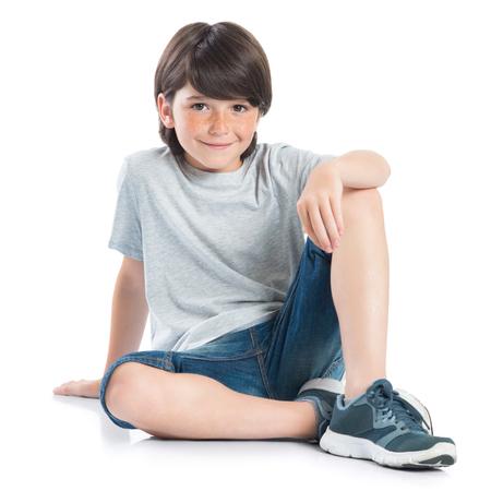 白い背景の上に座っている男の子を笑顔のクローズ アップ ショット。カジュアルなカメラ目線で愛らしい子です。床に座って、カメラを見て幸せな