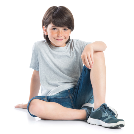 Closeup shot of smiling little boy sitting on white background. Adorable child in casual looking at camera. Happy cute boy sitting on floor and looking at camera. 版權商用圖片 - 48267685