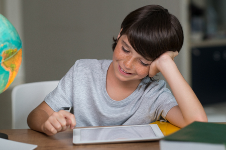 palmtop: Young boy using digital tablet at desk. Smiling kid looking at screen of palmtop. Little boy surfing the net with digital tablet. Young boy doing homework with digitaltablet. Stock Photo