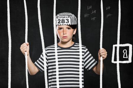 jail: Closeup of sad bad boy wearing jail suit and kept behind bars. Portrait of little prank in jail. Sad male kid wearing striped clothes.