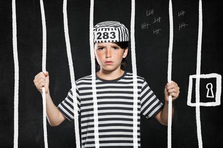 carcel: Primer plano de chico malo que desgasta el juego cárcel triste y se mantiene tras las rejas. Retrato de la pequeña broma en la cárcel. de hijo varón triste usan ropa de rayas.