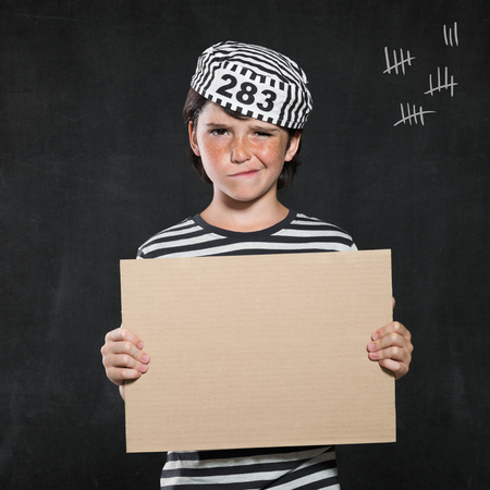scoundrel: Closeup mugshot photo of boy holding blank sign. Young boy make a face wearing jail suit isolated on black background. Little prisoner showing a cardboard.