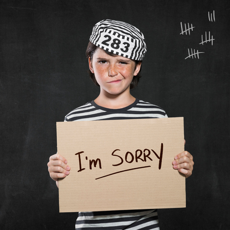 Closeup mugshot photo of boy holding I'm sorry sign. Young boy make a face wearing jail suit isolated on black background. Little contrite scamp showing his remorse.