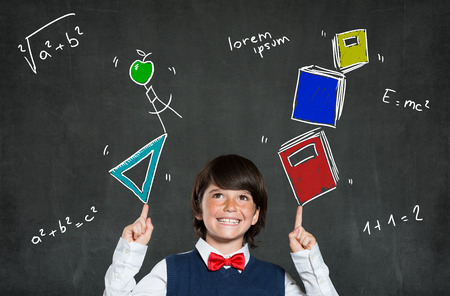 arms above head: Little boy playing with books and school instruments. Portrait of happy boy smiling and looking up. Cheerful cute child indicates formulas with arms raised above the head. Learning and education concept. Stock Photo