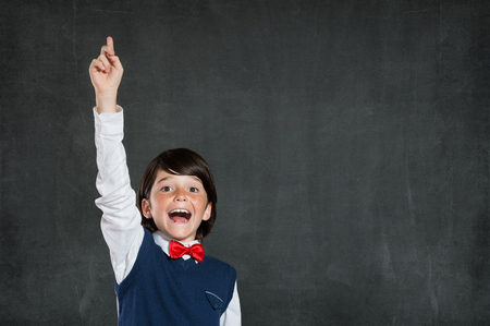 knowledge: Closeup of little boy with raised hand isolated on blackboard. Schoolboy pointing high his index finger. Cheerful cute boy with raised hand standing against black background.