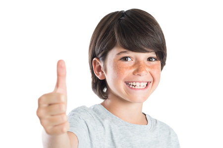 looking at: Closeup of smiling little boy showing thumb up gesture isolated on white background. Portrait of happy cute boy showing thumb up and looking at camera. Kid giving you thumbs up.