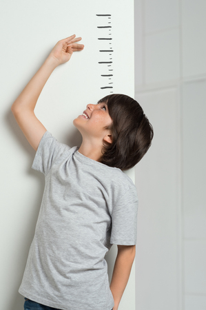 Closeup of little boy measuring height himself against white wall. Smiling cute boy measures his height. Boy growing tall. Young boy checking his height with the hand. Banco de Imagens