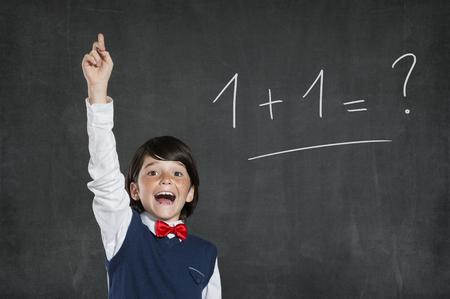 pizarron: Pequeño muchacho estudioso sabe la solución de este problema fácil. Colegial que apunta alto con el dedo índice. Lindo chico alegre con la mano levantada de pie contra el fondo negro. Foto de archivo