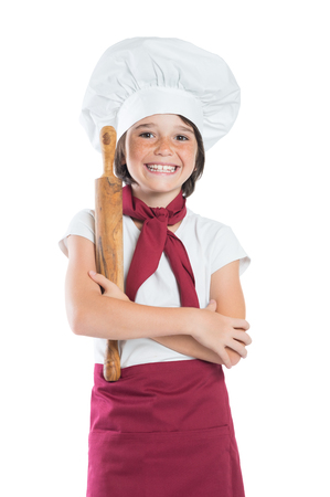 little: Closeup of smiling little boy dressed as chef isolated on white background. Little chef holding rolling pin and looking at camera. Happy cute boy dressed a cook.