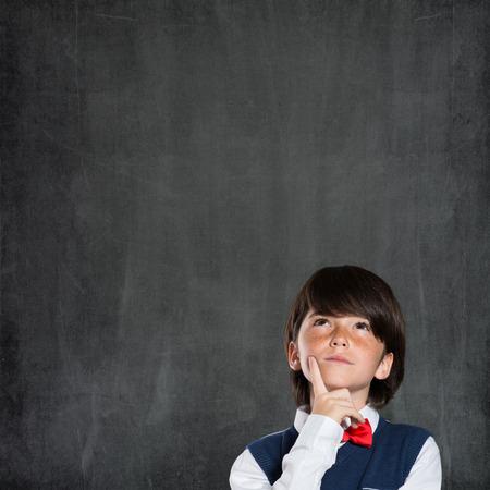jovenes estudiantes: Primer disparo de un ni�o que piensa con la mano en la barbilla aislados en la pizarra. Retrato de ni�o pensativo pensando en su futuro acad�mico. Ni�o tiene una idea.