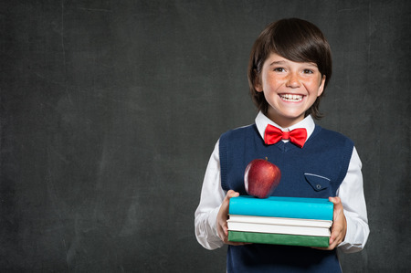 young boy smiling: Closeup of little boy holding stack of books and apple. Happy schoolboy smiling and looking at camera. Cheerful child holding books with red apple standing isolated on blackboard with copy space. Stock Photo