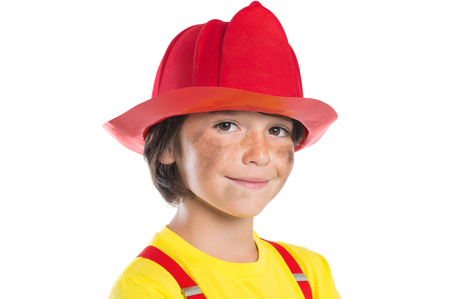 aspirational: Closeup face of smiling boy wearing firefighter helmet isolated on white background. Happy cute boy smiling and looking at camera with his face dirty soot. Stock Photo
