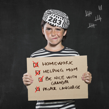 Closeup mugshot photo of boy holding sign with his bad behaviors. Young boy make a face wearing jail suit isolated on black background. Little prisoner showing a cardboard with his pranks.