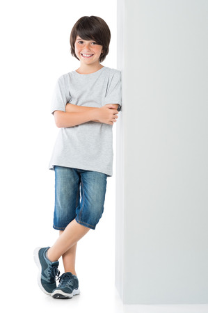 Lachende jongetje poseren tegen de grijze muur op een witte achtergrond. Gelukkig leuk kind dat zich tegen een witte achtergrond. Jongen leunend tegen een grijze teken en kijken naar de camera met armen gekruist.