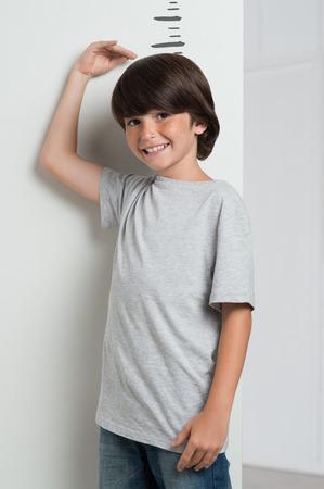 白い壁に対して彼自身の高さを測定男の子のクローズ アップ。成長背の高いボーイ。かわいい男の子を笑って頭を彼の手で彼の高さを測定します。