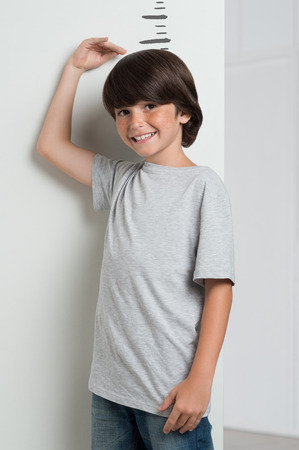 taller: Closeup of little boy measuring height himself against white wall. Boy growing tall. Smiling cute boy measures his height with his hand on the head. Happy growing boy looking at camera.