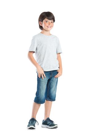 Lachende kleine jongen met sproeten staande op een witte achtergrond. Portret van tevreden schattig kind in casual kleding kijken camera. Gelukkig leuke jongen met de hand in de zak staande tegen een witte achtergrond.