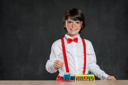 child boy: Smiling little boy doing an experiment. Young boy wearing protective glasses and playing with flasks for chemistry. Cheerful child doing an experiment with testtube isolated on blackboard.